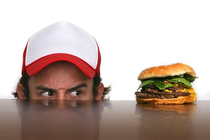 Chico mirando preocupado una hamburguesa